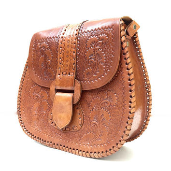 Vintage 1970s tan leather shoulder bag with intricate tooled panels and saddle stitched edging