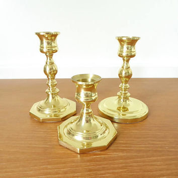 Three Baldwin Brass short candlesticks, brass candlestick centerpiece with octagonal bottoms