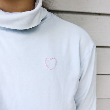 hand embroidered heart shape outline on pastel blue turtleneck