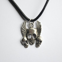 Gunmetal Winged Triple Skull Pendant attached to a Black Leather Necklace, arrives with satin pouch