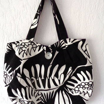 Fabric handbag with zipper pocket. Black and white floral print with purple lining.