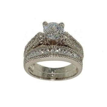 Designer Look Silvertone Two Piece Fashion Ring Wedding Set with High Mount Solitaire with Side Stones and Matching Wedding Band in Cubic Zirconia