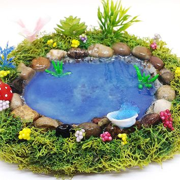 Fairy garden miniature pond. With shell fountain, blue water and plants.