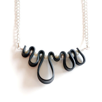 Black and white squiggle necklace handmade from recycled black rubber , white freshwater pearls and stainless steel wavy horizontal pendant