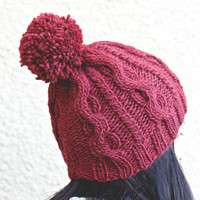 Knit hat for women in wine red color with cables and pompom