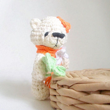 White crochet cute teddy bear with orange flower on ear, scarf decorated with white crocheted butterfly and symbol luck four leaf clover.