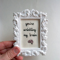 Wrinkling my brain cross stitch, completed cross stitch in small white ornate frame