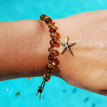 Boho crochet bracelet with brown and yellow glass beads a gold starfish clasped together with a upcycled vintage lucite button and tassel