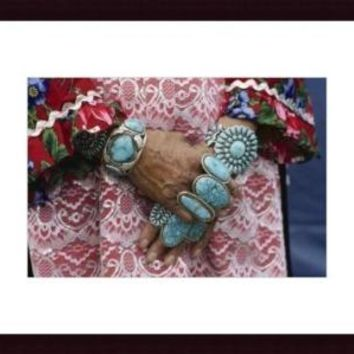 Heirloom rings and bracelets lie thick on arms and hands of Zuni woman, framed black wood, white matte