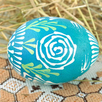 Handmade painted Easter egg with minimalistic ornament in blue colour palette