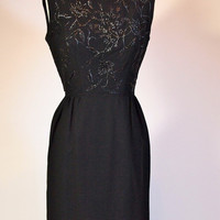 Vintage 1960s sleeveless black cocktail dress LBD by designer Susan Small with floral embroidery and beading with flap detail at back