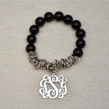 Vine Interlocking Monogram hanging on stretch string Bracelet made of black beads and silver mirror monogram