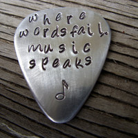 Guitar Pick hand stamped in aluminum-  ready to ship- where words fail music speaks