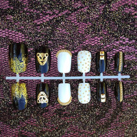 Classic elegant black and white lioness fake press on nails with gold glitter, chain, cheetah head, and stud detail