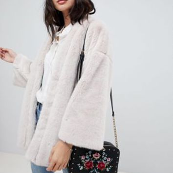 ASOS DESIGN reversible faux fur cape with floral print at asos.com