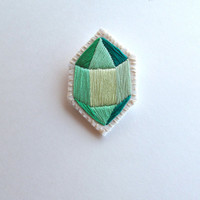 Green geometric brooch hand embroidered faux gem on cream muslin with a cream felt back silver pin