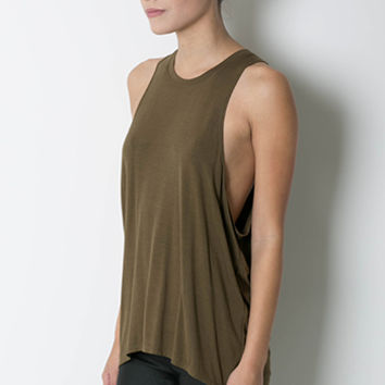 This super stretchy sleeveless muscle tank top features a round neckline, asymmetrical hemline, relax fit, wide opening arm hole. Pair with bandeau, denim shorts and gladiator.
