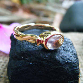Pale lilac amethyst cabochon in gold, ring features a decorative twisted wire shank.