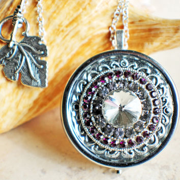 Music box locket, round locket with music box inside, in silver tone with purple rhinestones on front cover.