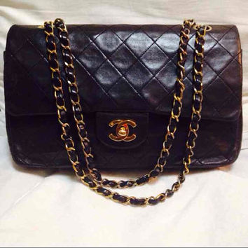 Vintage Chanel black 2.55 classic double flap purse with gold CC motif and gold chains. Lamb leather bag