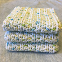 White cotton spa washcloths, with tiny yellow, light green and turquoise blue flecks.