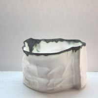 Crumpled paper looking white vessel made out of English fine bone china with burn looking finish.
