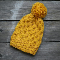 Knitted honeycomb hat for women in yellow gold color with pompom