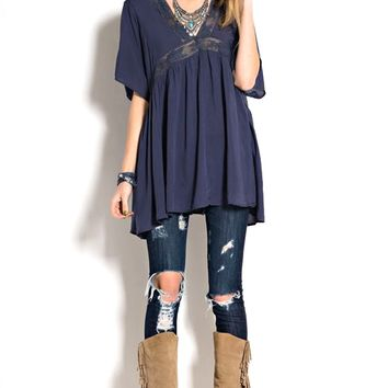 Featuring baby doll tunic top with short dolman sleeves and surplice back with self-ties at shoulder, plunging crochet lace v-neckline, oversize construction, semi-sheery fabrication, flowy tunic with pleated detailing at bodice. Unlined. Pair with knee cu