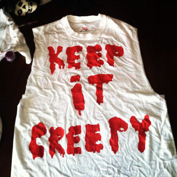 "White muscle tee ""keep it creepy"" painted on front"