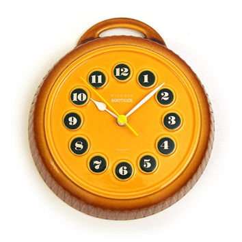 Ceramic wall clock. By KIENZLE Boutique. Burnt yellow / mustard colour earthenware. Junghans Quartz movement. Germany
