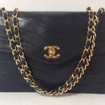 80s vintage Chanel black shoulder bag with gold tone chain strap and cc closure in unique squama shape stitch.  Rare and collectible. 2.55