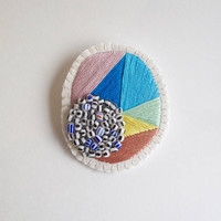 Hand embroidered jewelry geometric brooch bright colors of pink yellow green and blues with black and white African beads on cream muslin