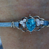 Bracelet with aqua pear shaped swarovski crystal surrounded with faux pearls on a silver tone background,blue leather strap with extension