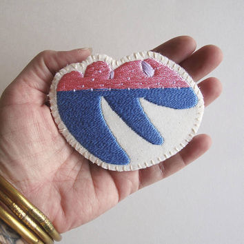 Hand embroidered brooch with unique geometric design using shiny pink and bright blue cotton thread An Astrid Endeavor textile jewelry