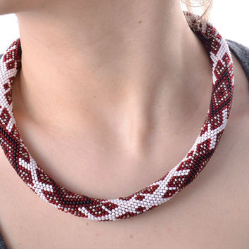 Handmade unique white beaded cord necklace with red patterns in ethnic style