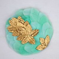 Katrine - Aquamarine fascinator headpiece made with feathers and golden fabric leaves