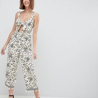 ASOS DESIGN floral jumpsuit with cut out and tie detail at asos.com