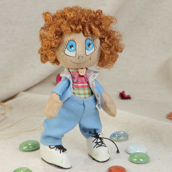 Handmade small funny soft doll with painted face and curly brown hair