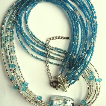Six Strand Necklace of Seed Beads Glass Bicones and a Fused Glass Square Pendant in Shades of  Aquamarine Aqua Blue and Silver