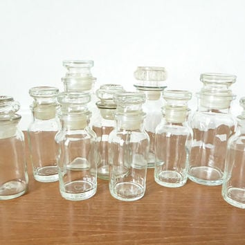 Ten vintage glass spice or apothecary jars with stoppers, various sizes