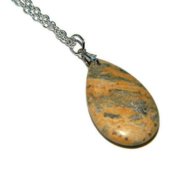 Polished tan teardrop stone necklace on silver tone chain