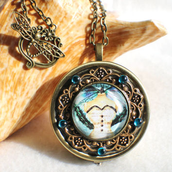 Music box locket,  round locket with music box inside, in bronze with steampunk fairy cabochon on front cover.