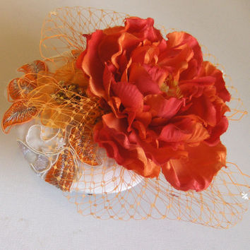 Cocktail hat, orange and ivory veiled.