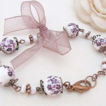 Copper bracelet with violet porcelain beads and ribbon bow
