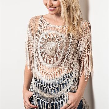 Featuring semi-sheer soft crochet, round neckline, short sleeves with fringe detailing, circle pattern crochet throughout, asymmetrical hemline with fringe finish.