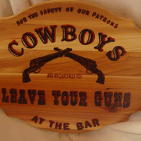 Cowboys Leave Your Guns At the Bar sign is wood burned on cedar and colored with Prisma Color pencils
