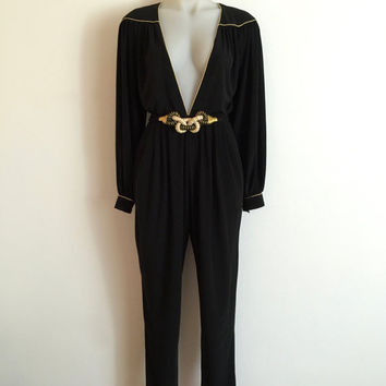 Vintage 1970s 'Masquerade' black micro jersey disco jumpsuit with plunging neckline, long sleeves and gold piping trims / Size 8