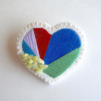 Hand embroidered heart brooch with bright colors of red, blues, green, lavender and serpentine beads on cream muslin with cream felt backing