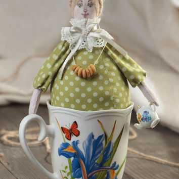 Handmade collectible fabric soft doll Tea Fairy in green dress sitting in a cup