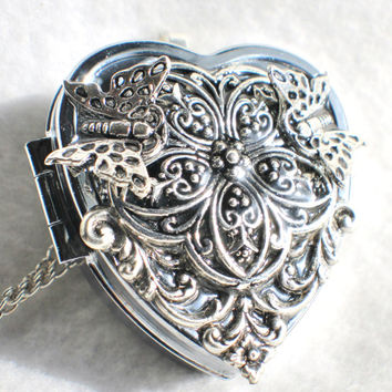 Music box locket,  heart shaped  locket with music box inside, in silver with silver filigree and butterfly's on front cover